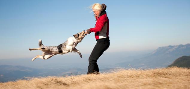 Kvinne som leker med hund på fjellet