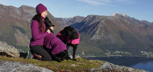 Kvinne med hunder på fjellet, med usikt utover fjorden
