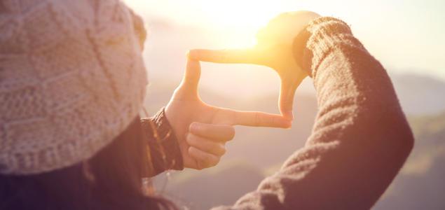 Jente som former fingrene som et vindu mot solen